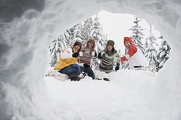 Austria, Salzburg, Men and women sitting at fire place in winter - HHF004219