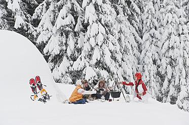 Austria, Salzburg, Men and women sitting at fire place in winter - HHF004228