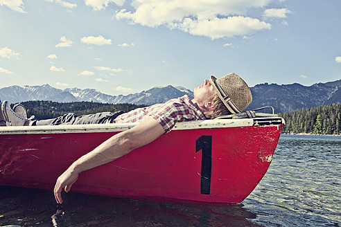 Germany, Bavaria, Mid adult man sleeping in rowing boat - RBF000935