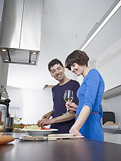 Germany, Cologne, Man and woman cooking together in kitchen - RHYF000118