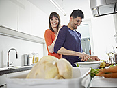 Germany, Cologne, Man and woman cooking together in kitchen - RHYF000133