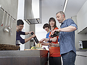 Germany, Cologne, Men and women cooking together in kitchen - RHYF000142