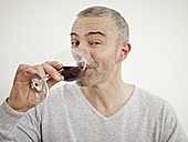 Germany, Cologne, Mature man drinking wine in kitchen, portrait - RHYF000178