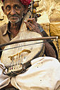 India, Rajasthan, Jaisalmer, Begging musician at Jaisalmer Fort - MBE000395