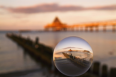 Germany, Usedom, Heringsdorf, Reflection of lake and bridge in glass sphere - VDSF000004