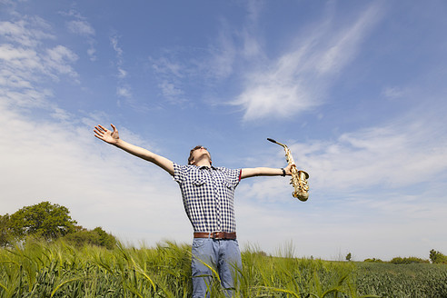 Germany, Hamburg, Teenage boy stretching arms and holding saxophone in nature - MSF002681