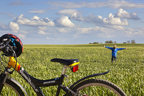 Germany, Hamburg, Boy standing and stretching arms in field, bicycle in foreground - MSF002685