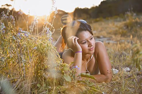 USA, Texas, Concan, Teenage girl lying on meadow with head phones - ABAF000035