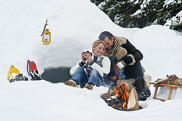 Austria, Salzburg County, Couple sitting near fireplace - HHF004259