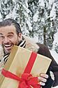 Austria, Salzburg County, Mature man standing with christmas parcel, smiling, portrait - HHF004266