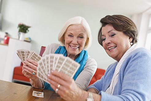 Germany, Leipzig, Senior women playing card game, smiling - WESTF018765