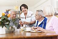 Germany, Leipzig, Senior men and women eating food, smiling - WESTF018786