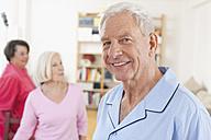 Germany, Leipzig, Senior man smiling, women standing in background - WESTF018795