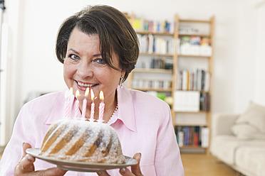 Germany, Leipzig, Senior woman holding birthday cake - WESTF018801