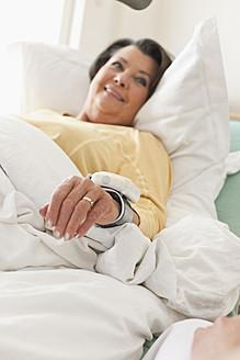 Germany, Leipzig, Senior woman lying on medical bed, smiling - WESTF018819