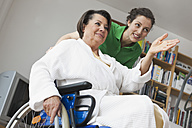 Germany, Leipzig, Senior woman sitting on wheelchair while another woman pushing - WESTF018837