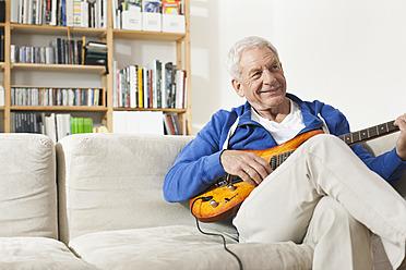 Germany, Leipzig, Senior man sitting on sofa and plucking guitar - WESTF018879