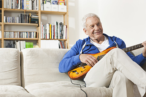Germany, Leipzig, Senior man sitting on sofa and plucking guitar - WESTF018879