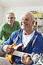 Germany, Leipzig, Senior man playing electric guitar, man sitting in background - WESTF018882