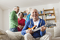 Germany, Leipzig, Senior man playing electric guitar, man and woman in background - WESTF018888