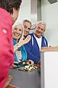 Germany, Leipzig, Senior men and women cooking food - WESTF018897