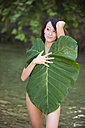 Young woman covering herself with elephant ear plant - ABA000073
