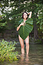 Young woman covering herself with elephant ear plant - ABA000074