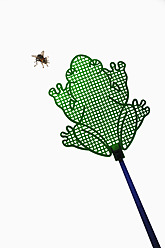 Frog shaped fly swatter with fly on white background, close up - AXF000090
