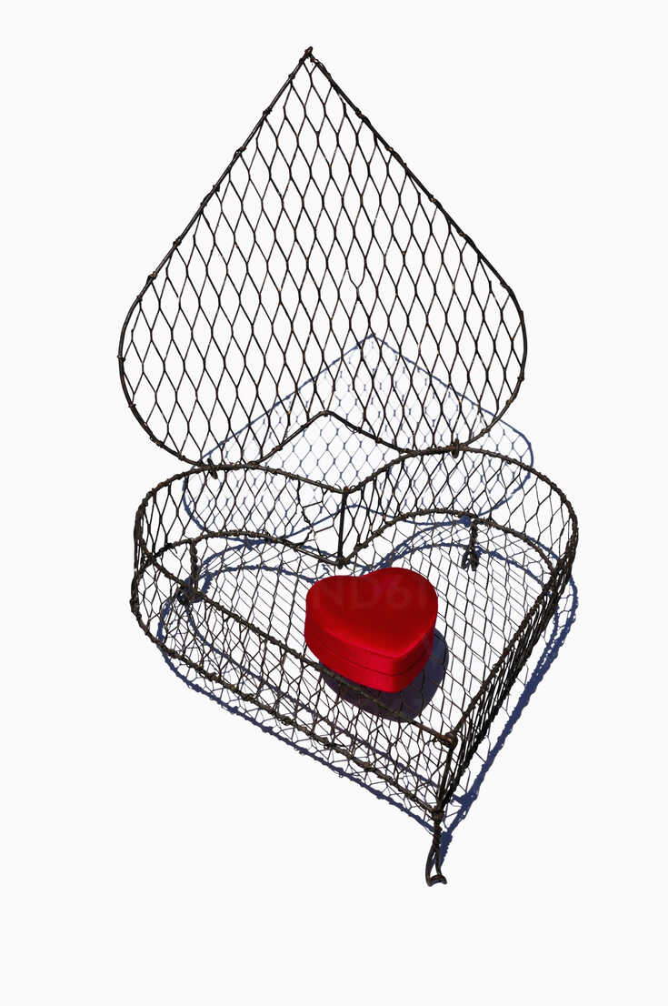 Heart shape cage made by wire with red heart on white background, close up - AXF000094 - Axel Ganguin/Westend61