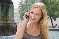 Germany, Bavaria, Munich, Young woman talking on phone in front of Ludwig Maximilian University - TCF002800