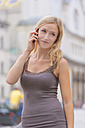 Germany, Bavaria, Munich, Young woman talking on phone in front of Ludwig Maximilian University - TCF002807