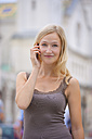 Germany, Bavaria, Munich, Young woman talking on phone in front of Ludwig Maximilian University - TCF002808