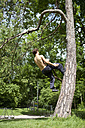 Germany, Bavaria, Young man doing parcour training in park - MAEF004797