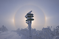 View of sundog with directional sign in snowy landscape - RUEF000888