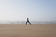 Belgium, Young woman exercising at North Sea - GWF001864