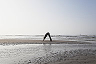 Belgium, Young woman exercising at North Sea - GWF001870