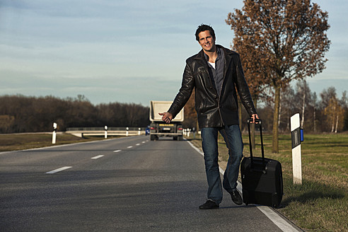 Germany, Bavaria, Munich, Mid adult man hitchhiking on road - RDF001002
