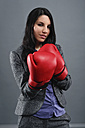 Young woman wearing boxing gloves, portrait, close up - RDF001019