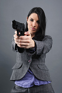 Young woman wearing holding gun, portrait, close up - RDF001022