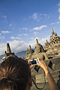 Indonesia, Young woman taking photo of Buddha statue at Borobudur Temple - MBEF000408