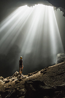 Indonesia, Young woman looking at sunbeam - MBE000419