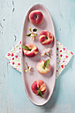 Peaches on ceramic platter with blossom on table - ECF000007