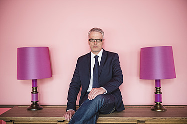 Germany, Stuttgart, Businessman sitting on sideboard with lamps, smiling, portrait - MFP000124