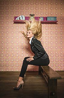 Germany, Stuttgart, Businesswoman sitting on bench, waving hair - MFP000145