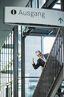 Germany, Stuttgart, Businessman moving up on office staircase, portrait, smiling - MFPF000199