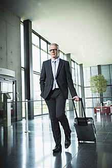 Germany, Stuttgart, Businessman pulling luggage in office building - MFPF000208