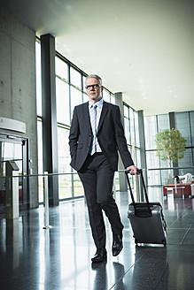 Germany, Stuttgart, Businessman pulling luggage in office building - MFPF000208