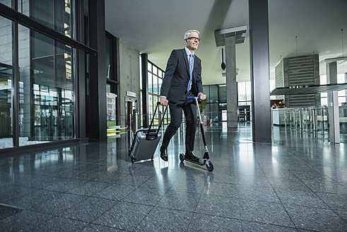 Germany, Stuttgart, Businessman using scooter while pulling luggage in office building - MFPF000211