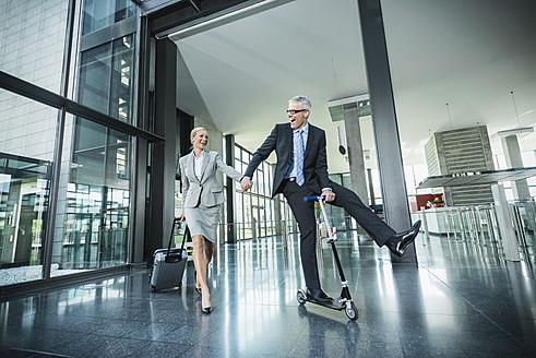 Germany, Stuttgart, Businesswoman with wheeled luggage, man riding scooter at office building - MFPF000214