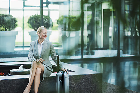 Germany, Stuttgart, Businesswoman sitting with wheeled luggage, smiling - MFPF000217